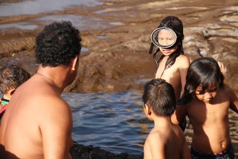"""Après l'école, Pierre, l'instituteur de la petite classe multi-niveaux de CP-CE2 amène les enfants sur le littoral. Ils apprennent à se servir des masques et des tubas.  Une fois à l'aise, les enfants cherchent des petits poissons à observer, identifier, ou encore à attraper pour les étudier dans leur aquarium en classe.   Ils mènent ici depuis 2014, le projet d'Aire Marine Éducative: interdiction de pêcher dans une partie de la baie durant 5 ans, le temps que les poissons se reproduisent.  Si les habitants ne respectent pas les prescriptions, alors, ce sont les enfants qui décident des sanctions.   C'est la remise au goût du jour du """"ahui"""", une pratique traditionnelle de gestion des ressources imposant aux habitants de respecter les périodes de pêche et les périodes d'interdiction (les """"tapu"""").  Si les interdictions n'étaient pas respectées, le chef de la tribu pouvait décider de la mise à mort du """"voleur"""" !   Aujourd'hui, il s'agit plutôt de coupures d'électricité ou de confiscation du matériel de pêche... !   Les enfants apprennent à connaître l'océan, à le vivre et à le gérer. Ils deviennent de vrais citoyens dont la voix pèse dans les décisions communales, en ce qui concerne la gestion des ressources de la vallée."""