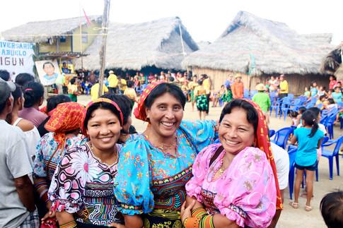 Lucy et ses amies prennent la pause alors que derrière elles des danseurs et musiciens interprètent une danse traditionnelle Kuna, à l'occasion de la fête de Yaigun, un des instigateurs de la révolution Kuna.  La tenue traditionnelle des femmes kuna est agrémentée d'un mola, une pièce de tissu cousu à leurs chemisiers. Le mola est un objet d'art réalisé par les femmes. C'est une pièce constituée de plusieurs couches de tissu de différentes couleurs. Chaque mola est unique et peut représenter différents sujets, selon le bon vouloir de sa créatrice: animaux, plantes, réels ou imaginaires inspirés de la cosmovision kuna. Les femmes peuvent mettre 4 mois à réaliser un seul mola.