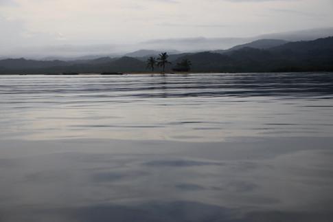"""Une minuscule île où une maison a été construite afin de permettre aux agriculteurs d'y séjourner lors de longues périodes de travaux au """"campo"""".  Ce matin, nous glissons en pirogue sur une mer d'huile. L'orage a grondé toute la nuit."""