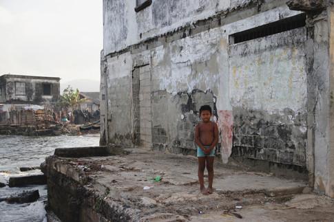 Depuis les années 80, de plus en plus de maisons en béton se construisent, à la place des traditionnelles huttes en bois. Le sable des plages de l'île a été tellement utilisé pour les construire qu'il a disparu. Ici, un enfant pose devant le bâtiment administratif de l'île, dont les fondations se retrouvent dans l'eau.