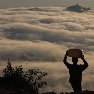 Un homme descend des marchandises depuis le sommet. En contrebas, la mer de nuages recouvre le lac Batur.