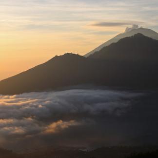 """Derrière la caldeira du Mont Batur et le volcan Abang (2 152m), à 12km environ, le monstrueux cône volcanique d'Agung d'où une épaisse fumée blanche s'échappe.  Ce volcan est le plus haut (3 142 m) et le plus important de l'île. Agung, signifie """"roi"""" en indonésien. Demeure des dieux, les habitants le vénèrent et le respectent autant qu'ils le craignent. En effet, la dernière éruption datant de 1963 avait fait des milliers de morts et d'énormes dégats.   Nous avons pu l'apercevoir depuis le volcan Batur à 1717m."""