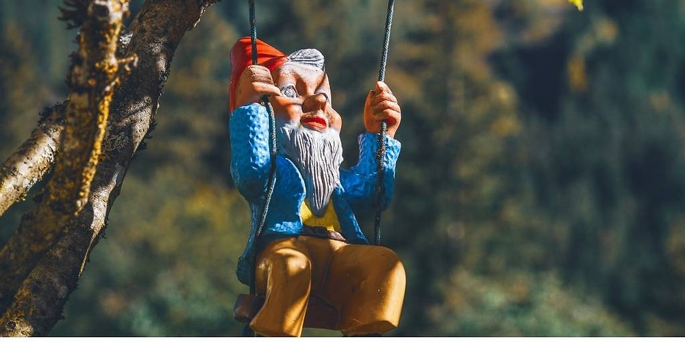 Picture of a garden gnome wearing a red hat, blue coat, and cacies sitting on a swing