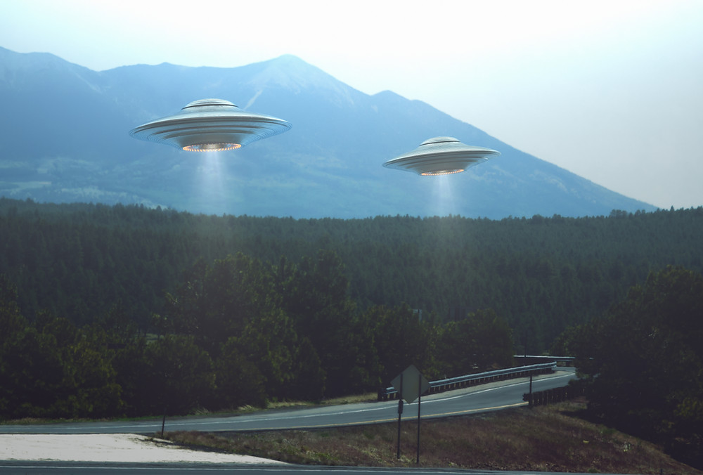 two UFOs flying over a winding mountain road and forested area
