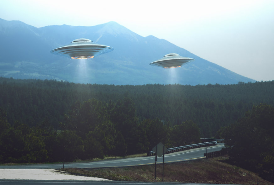 Banner image of UFOs flying over a forest and mountian range