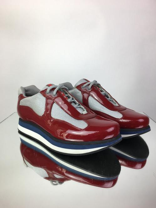 40c1d629249a5 Tênis PRADA, confeccionado em couro envernizado, tecido e borracha, nas  cores vermelha, cinza, azul e branco. O tênis possui solado mais alto, ...