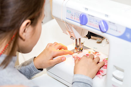 Little girl using sewing machine to make