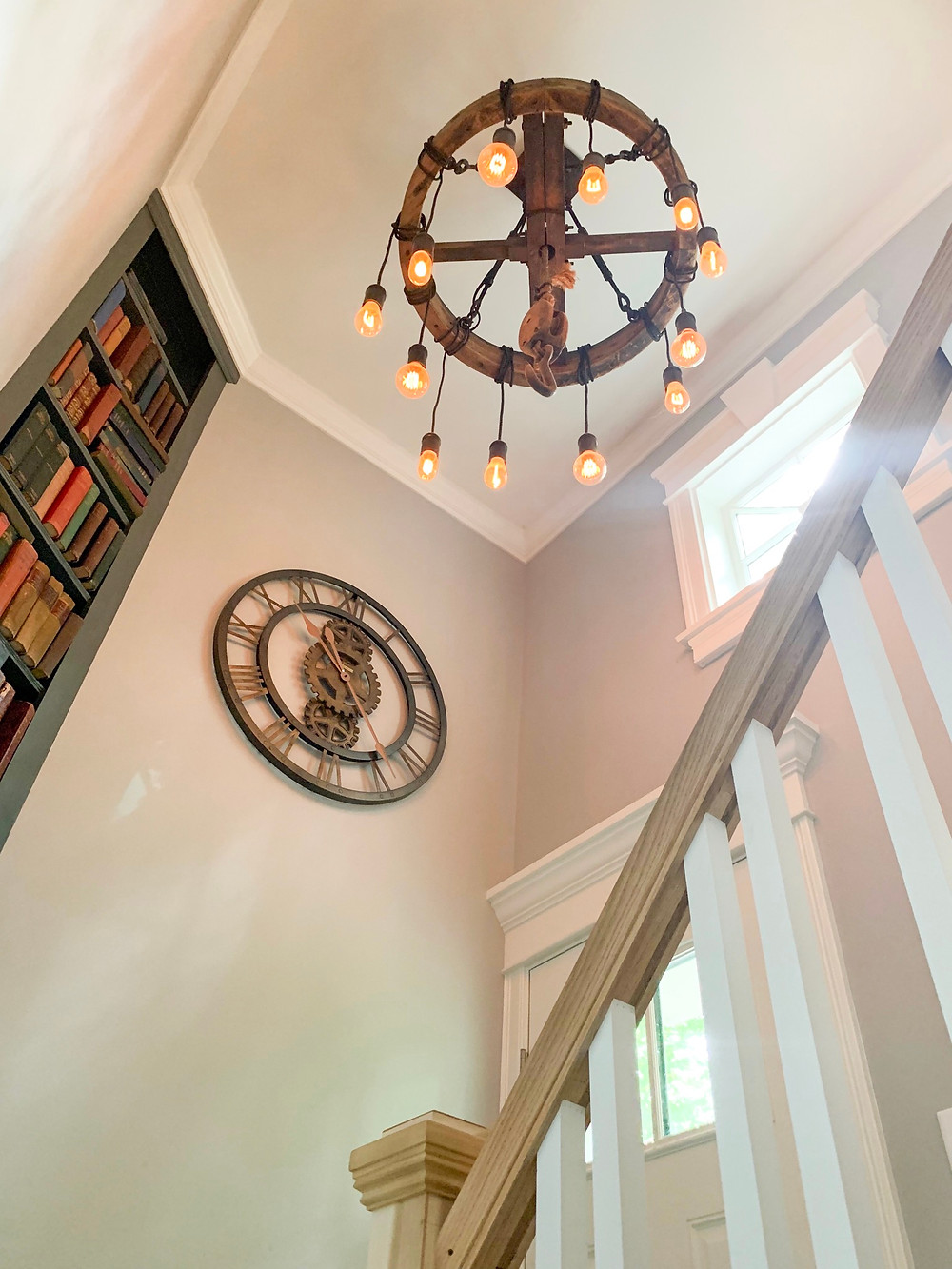 Repurposed Vintage Wheel Barrel is the base structure to this Custom Lighting Fixture with Edison Bulbs which illuminates the stairway at the original Manville Library in Lincoln, MA, now a residence.