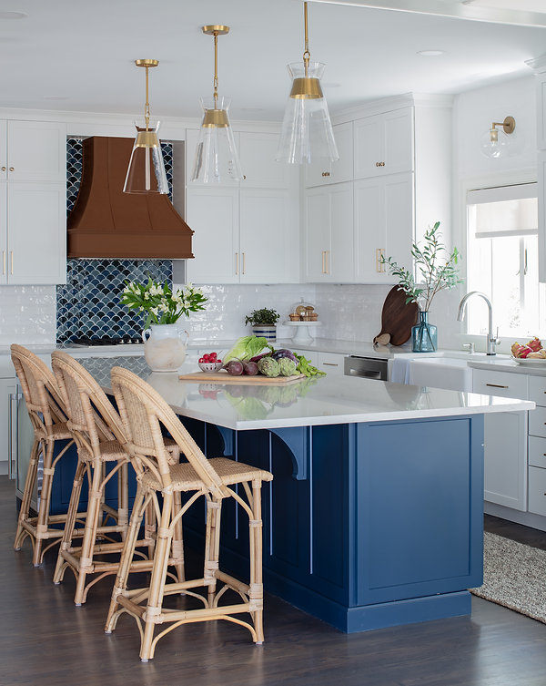 A bright and coastal inspired kitchen with a fun fish scale accent tile above the range. The Walnut hood adds a touch of rustic charm to this oceanfront property.