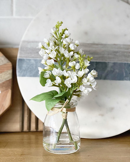 A faux syringa in a glass vase