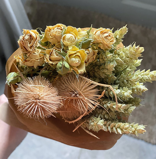 Dried bunch of wheat, thistles and yellow flowers