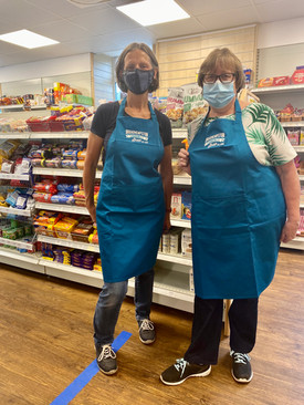 2 volunteers showing off our new aprons