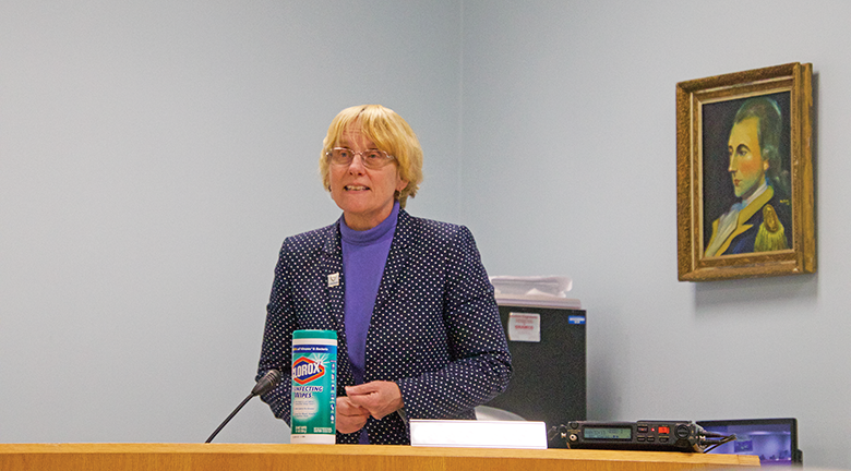 Carey has a container of Clorox disinfecting wipes, addresses the Montgomery Township Board of Health on March 11. A portrait of the township's namesake, General Montgomery, is in the background.