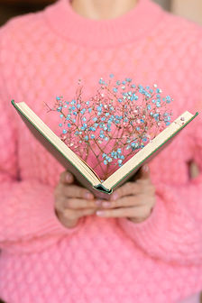 woman-holding-an-open-book-with-a-bouquet-of-dried-flowers-inside.jpg