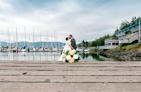 bride and groom on pier at john wayne marina