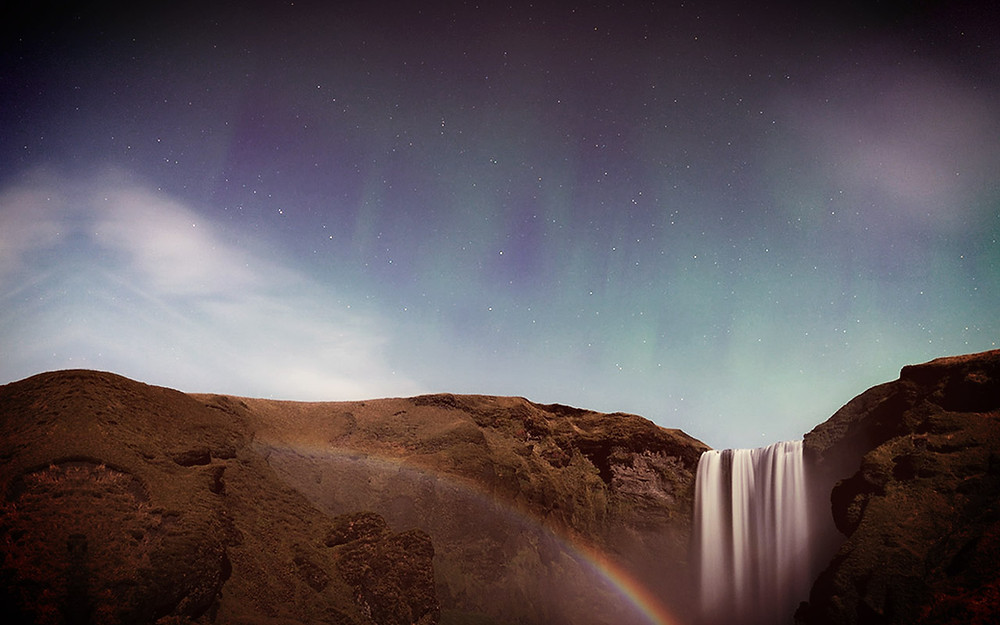 Rock face with waterfall, rainbow and dramatic star lighting in sky.