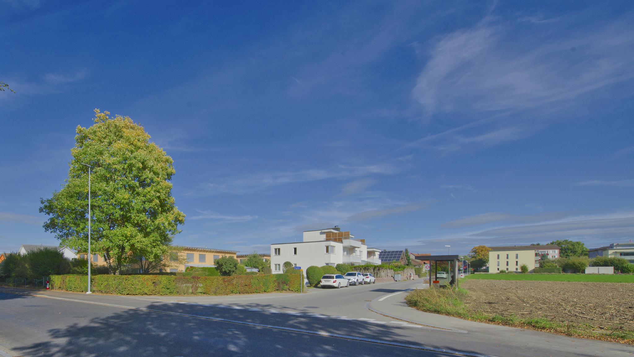 Das Mehrfamilienhaus mit dem freien Land und der Bushaltestelle