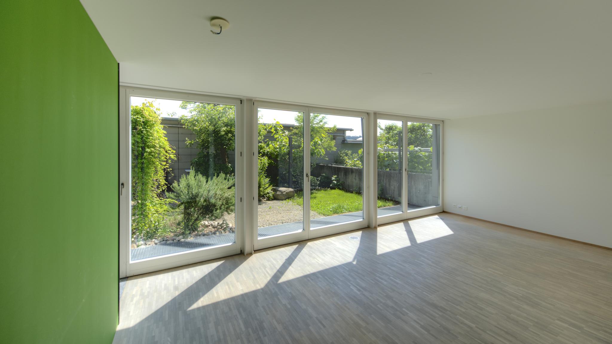 """Wohnzimmer mit Blick in den """"atriumartigen"""" Garten"""