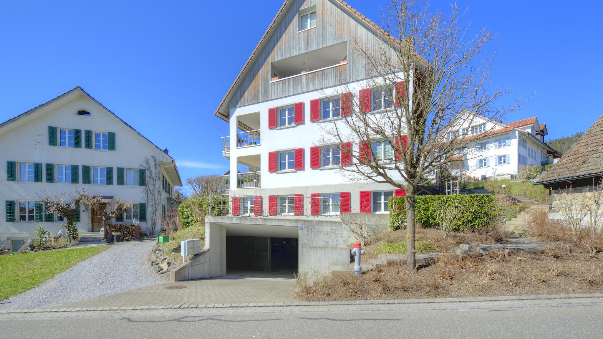 Ansicht des Mehrfamilienhauses mit der Garagenzufahrt