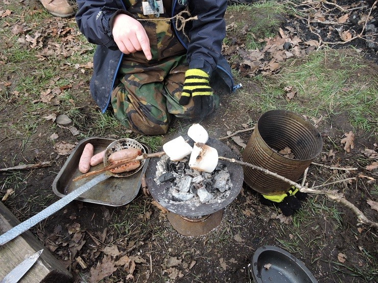 Children cooking using a charcoal pot at a forest school