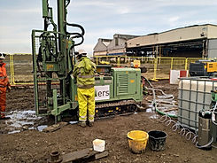 A technician working on a drill rig to inject remediation reagents