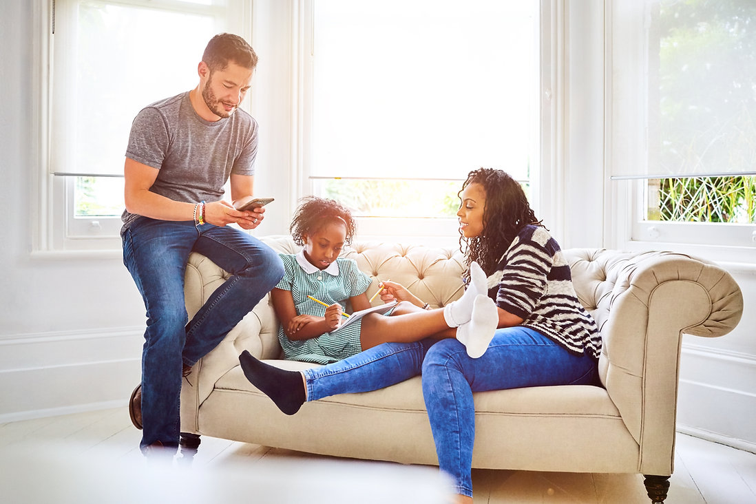 Protea Wellness family therapy - white transgender man and Black cisgender woman with a mixed race girl child sitting on a couch