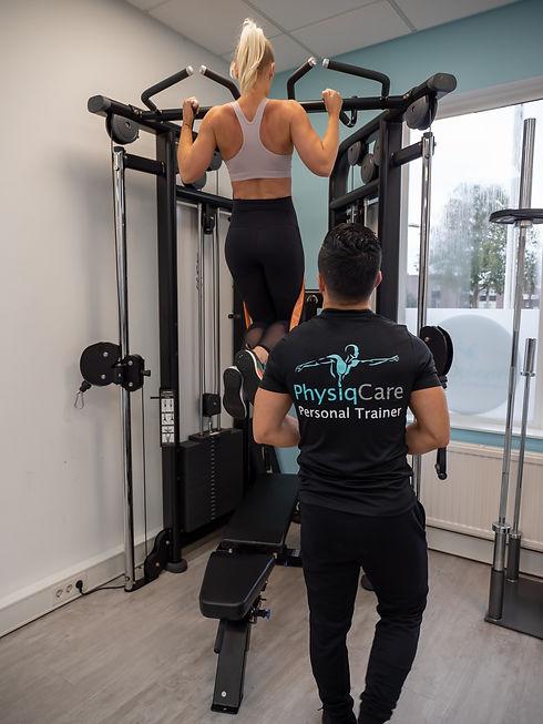 Personal trainer kijkend naar cliënt dat bezig is met training