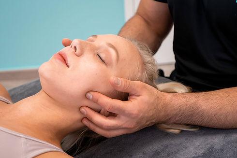 Vrouw ontvangt Orofaciale fysiotherapie aan haar kaak