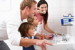family at sink brushing teeth