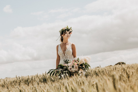 Rustic romantic barn wedding. Bride in corn field