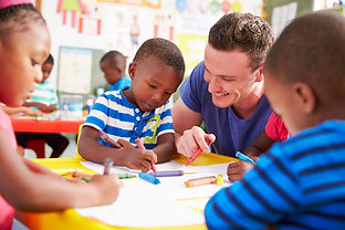 Volunteer teacher helping a class of pre