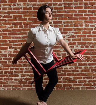 Woman standing with chair around her waist.