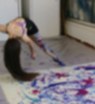 Female dancer painting on canvas with her legs, dancing across the canvas.