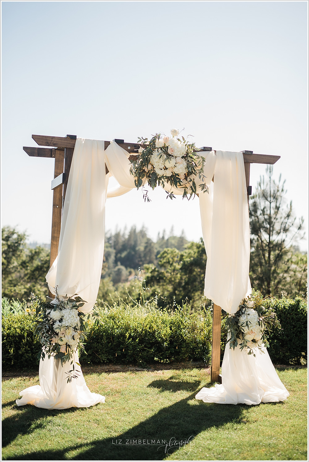 Wooden wedding arch with fabric and floral swags