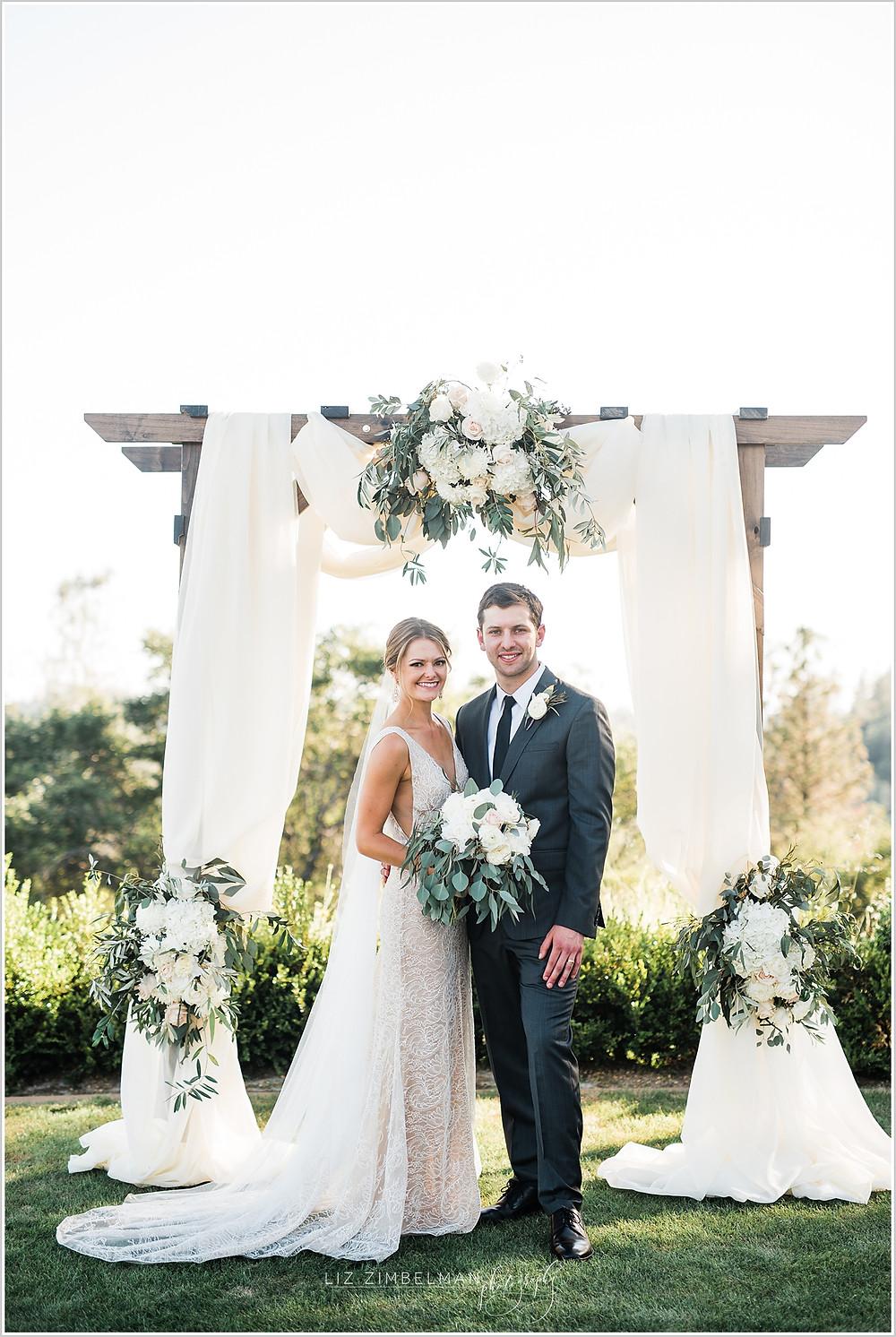 Bride and groom posing beneath wedding arch
