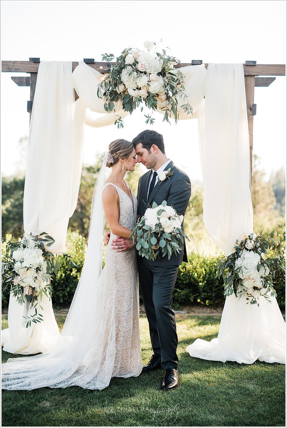 Bride and groom beneath wedding arch