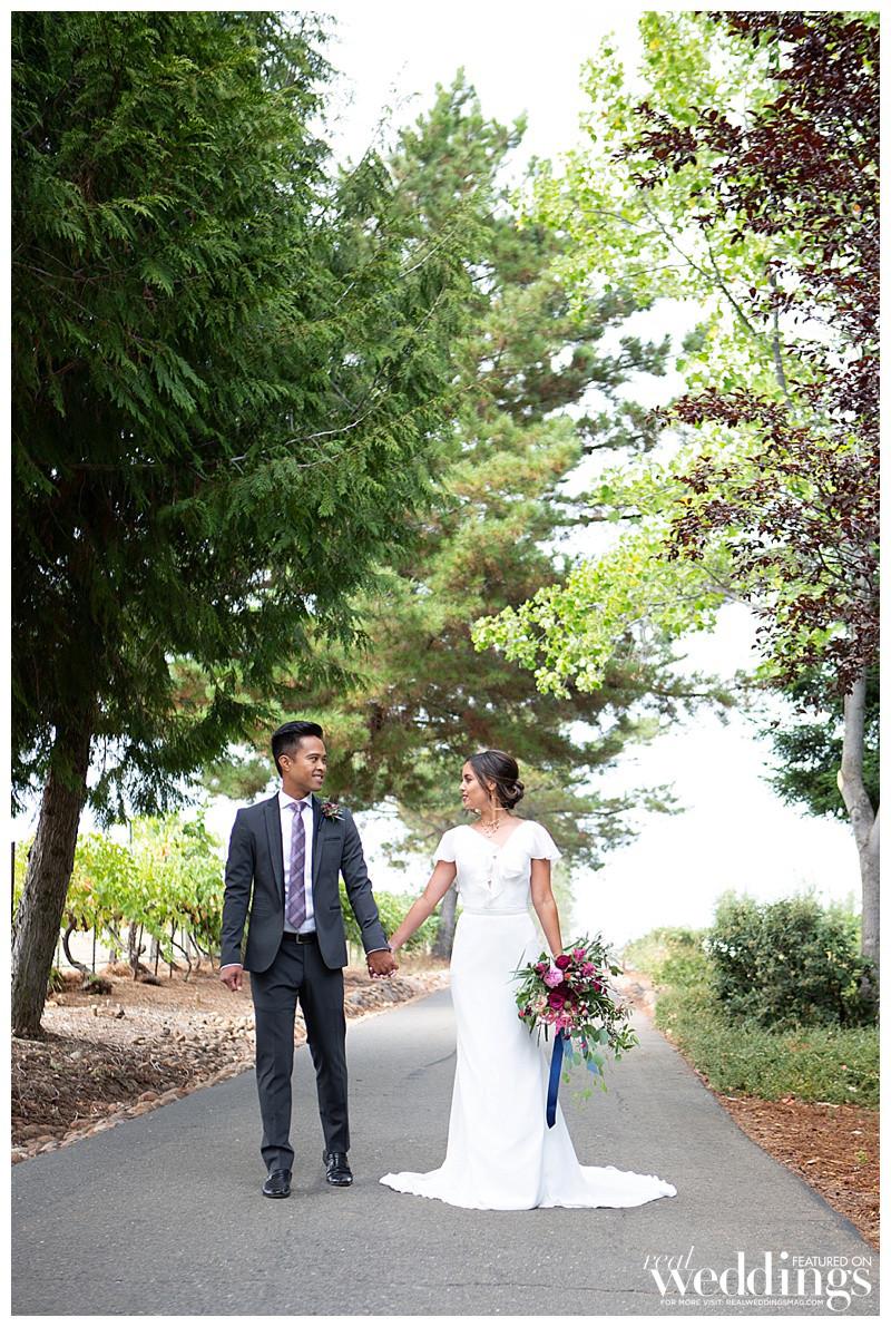 Bride and groom walking down path at Avio Winery