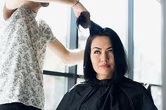 unrecognizable-hairdresser-creating-hair