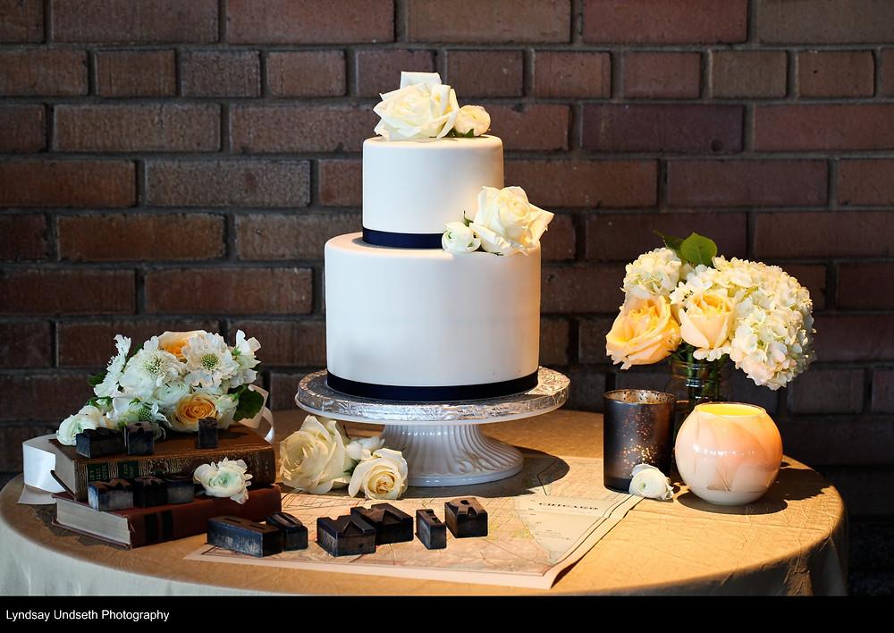 White roses adorn crisp navy and white cake | Wedding flowers by Visual Impact Design, Sacramento Wedding Florist | Kate Whelan Events | Lyndsay Undseth Photography | Citizen Hotel Wedding Reception