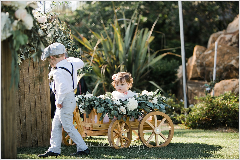 Ring bearer pulling flower girl in wagon