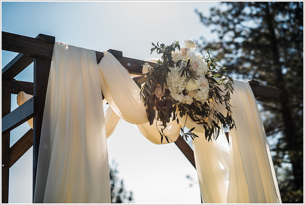 Close up of wedding arch with fabric and center floral swag
