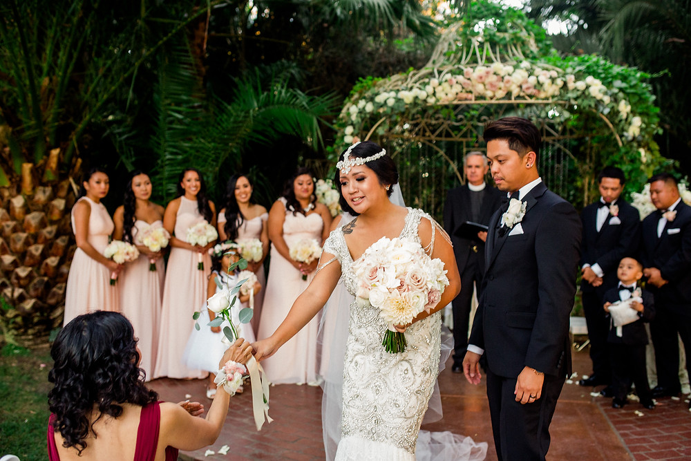 Bride giving flower to wedding guest