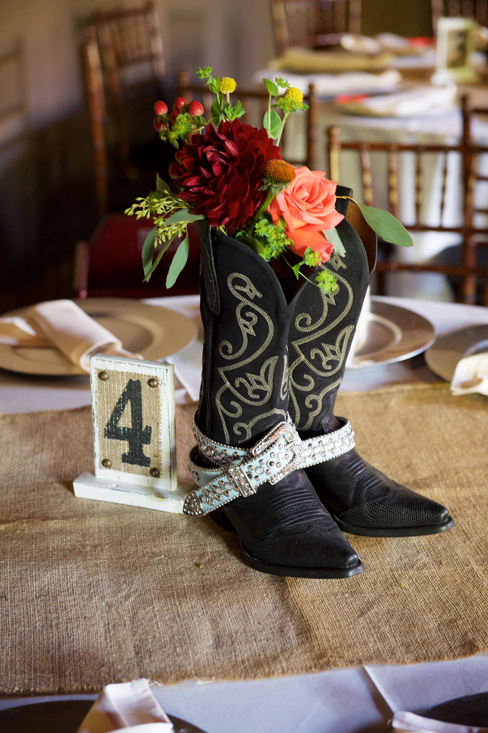 Country barn wedding. Cowboy boot centerpieces with flowers! Wedding colors were an earth tone palette of burgundy, rust, yellow, brown and green by Visual Impact Design. Sharpe Wedding Photography.