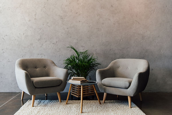 Two cozy grey armchairs standing on white carpet in empty room.jpg