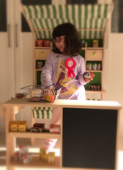 niña jugando en la cocina de juguete