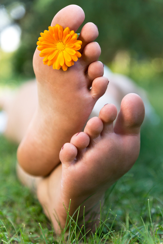 Feet with an orange flower between the toes