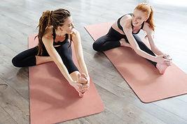 Les femmes sur le tapis de yoga stretching