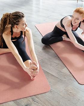 Les femmes sur le tapis de yoga stretchi