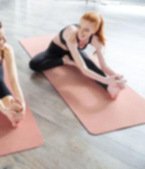Frauen Stretching auf Yoga-Matte