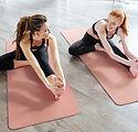 Vrouwen die zich uitstrekt over Yoga Mat
